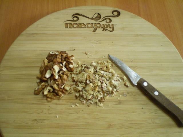 Грецкие орехи освободите от кожуры и мелко подробите. Сделать это можно при помощи ножа или с помощью ступки.