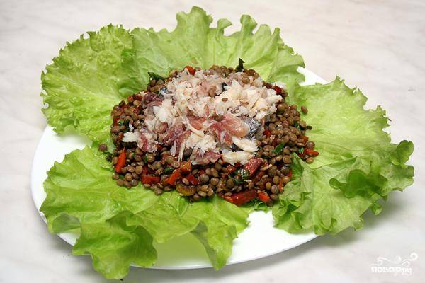 На листья салата выкладываем чечевицу с овощами, сверху - кусочки рыбы. Готово!