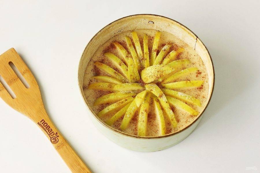 Сверху разложите нарезанное дольками яблоко, слега вдавливая их в тесто. Посыпьте яблоки сахаром и корицей по вкусу. Запекайте в разогретой до 180 градусов духовке около 35 минут.