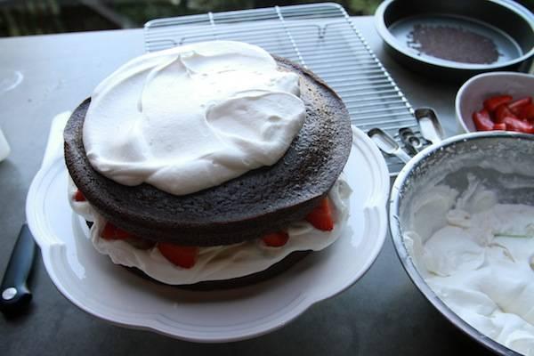 7. Накрыть вторым коржом, снова смажем кремом, выложим ягоды. При желании оформить клубнично-шоколадный торт в домашних условиях можно кремом со всех сторон или шоколадом, например.