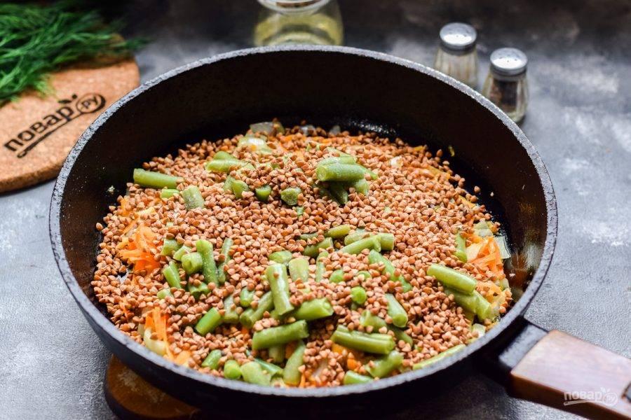 Следом всыпьте в сковороду гречневую крупу, добавьте соль и перец по вкусу.