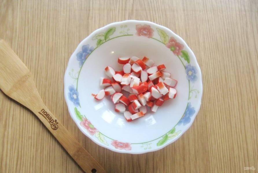 Крабовые палочки нарежьте небольшими кубиками и выложите в салатник.