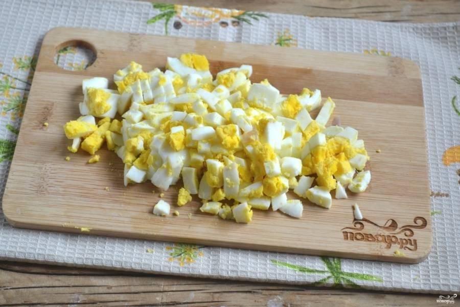 Отваренные вкрутую яйца порежьте кубиком.