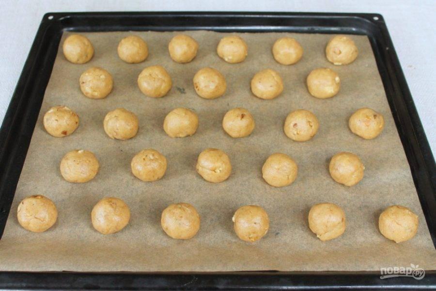 Пряничное тесто с орехами разделяем на части. Делаем шарики и кладем их на противень в шахматном порядке.  Запекаем при температуре 190 градусов около 15 минут.