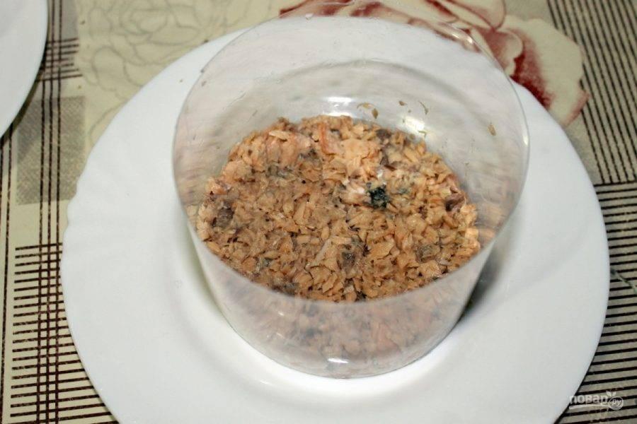 На дно тарелки по форме выкладываем рыбную консерву.