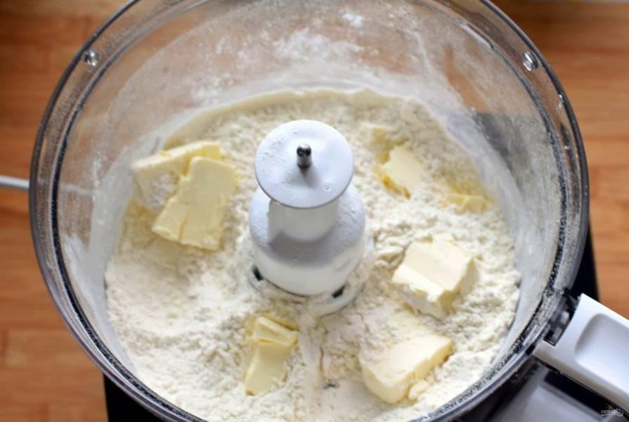 Начать лучше с приготовления песочного теста. Я всегда готовлю его с помощью кухонного комбайна. Это легко, быстро и качественно. Положите в чашу просеянную с разрыхлителем  и солью муку, добавьте нарезанное кусочками холодное масло. Пробейте в пульсовом режиме в крошку.
