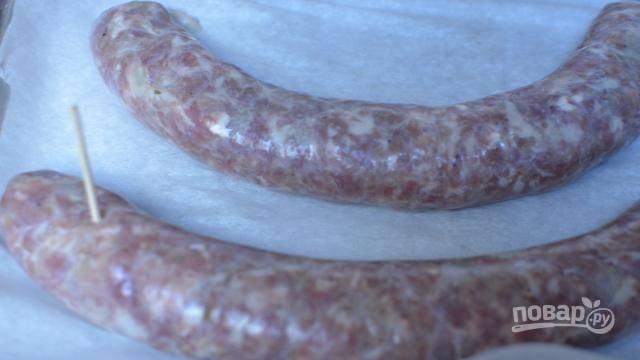 6. Выложите их на противень, застеленный пергаментом и смазанный небольшим количеством масла. Сделайте иголкой или зубочисткой несколько проколов, чтобы колбаски не лопнули. Отправьте в разогретую духовку и запекайте при 200 градусов примерно полчаса (время зависит от размера колбасок и желаемой корочки).