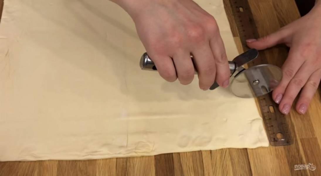 1. Слоеное тесто выложите в один слой на столе. Разрежьте его на длинные полоски шириной 3 см. Половину полоски посыпьте тертым сыром, накройте второй половиной полоски и защипните края.
