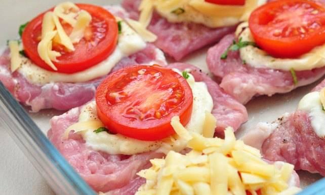 Затем кладем кружочек помидора и посыпаем натертым сыром. Накрываем фольгой и запекаем блюдо 60 минут. Затем снимаем фольгу и запекаем еще 10-15 минут.