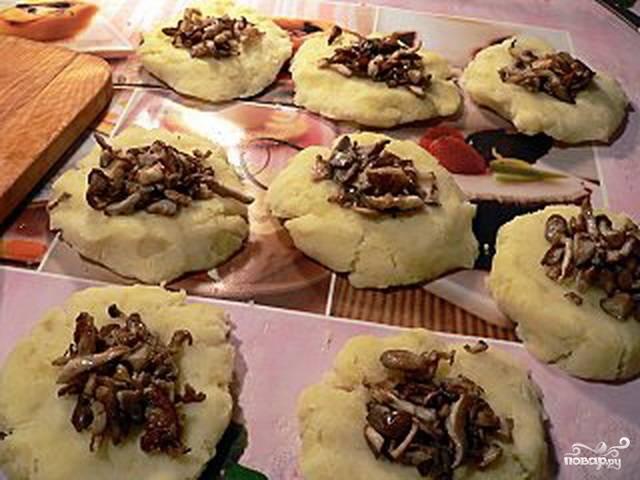 Получившееся тесто делим на порции и из каждой делаем лепешку. На каждую лепешку выкладываем грибную начинку.
