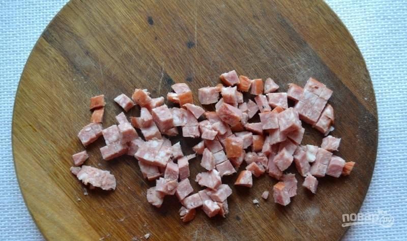 5.Копченую колбаску нарежьте кубиками, можно кружочками или полукольцами.