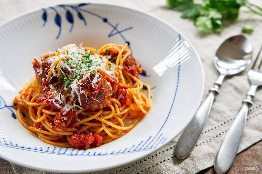 8.Отварите спагетти в подсоленной воде, затем откиньте на сито. Переложите спагетти в тарелку и выложите на них томатный соус с мясными шариками. Украсьте петрушкой и тертым сыром, ешьте все сразу.