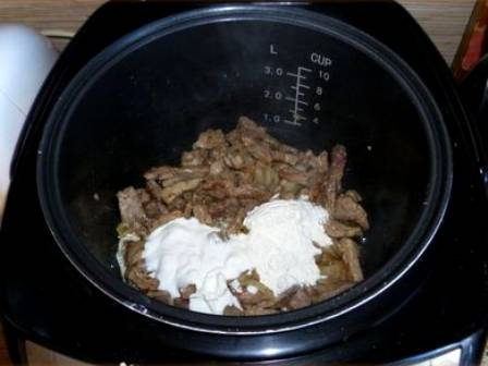 Режим «Жарка» выключаем и выкладываем в чашу мультиварки сметану, томатную пасту, насыпаем муку, вливаем стакан воды, перемешиваем все, чтобы не осталось мучных комочков, и солим соус по вкусу. Выбираем в мультиварке режим «Тушение», устанавливаем время 25 минут и готовим бефстроганов под крышкой.