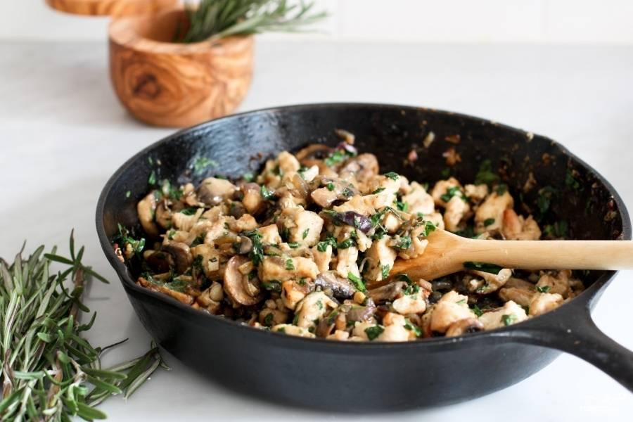 Нарубите мелко красный лук, выложите в ту же сковороду, в которой обжаривали куриное филе. Жарьте лук до мягкости, это около пяти минут. Если понадобится, налейте ещё немного оливкового масла. Затем выложите к луку рубленный чеснок (лучше его мелко нарежьте, выдавленный он просто даёт сок, а жареный чеснок хорошо сочетается с луком и грибами). Обжаривайте минуты 2. Потом нарежьте грибы и розмарин. Добавьте к луку с чесноком. Посолите и потушите всё вместе 10 минут. Затем шпинат. Можете нарезать его крупными кусками или нарвать. Когда шпинат станет мягче, добавьте курицу. Помешайте. Потушите ещё немного, как только шпинат совсем размягчиться, уберите сковороду с огня.