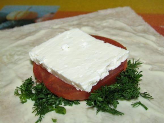 1. Лаваш нарезаем квадратами среднего размера., каждый из которых смажем сметаной или соусом, можно посыпать специями. Выкладываем измельченную зелень, потом тонкий ломтик помидора и кусочек брынзы. Заворачиваем края, чтобы получились конвертики.