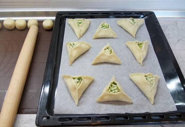 8. Противень застелить бумагой и выложить пирожки. Отправить их в разогретую духовку и выпекать до готовности.  Дополнить этот простой рецепт пирожков из заварного теста можно кунжутом, например.