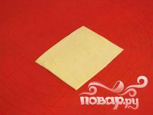 Раскатать слоеное тесто, вырезать из него прямоугольник.