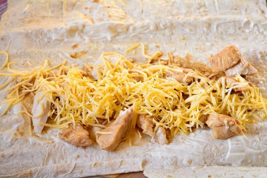Присыпьте куриную начинку слоем сыра.