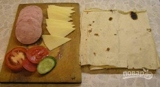 1. Лаваш разрежьте на 6 равных квадратов, подготовьте все ингредиенты для начинки. Для соуса смешайте майонез и сметану, добавьте пропущенный через пресс чеснок и измельченный укроп.