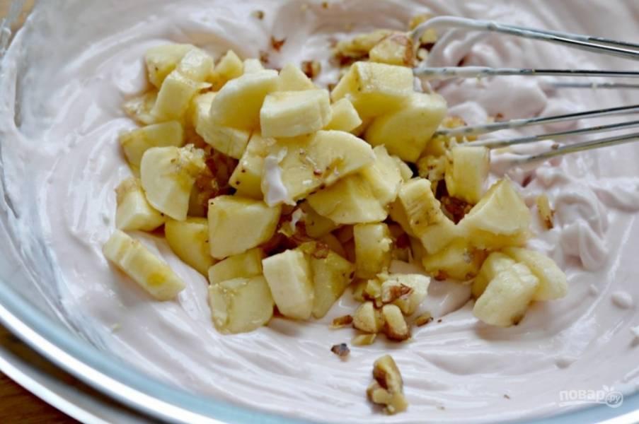 Банан порежьте кружочками. Орехи очистите и наломайте некрупно. Банан и орехи отправьте в крем.