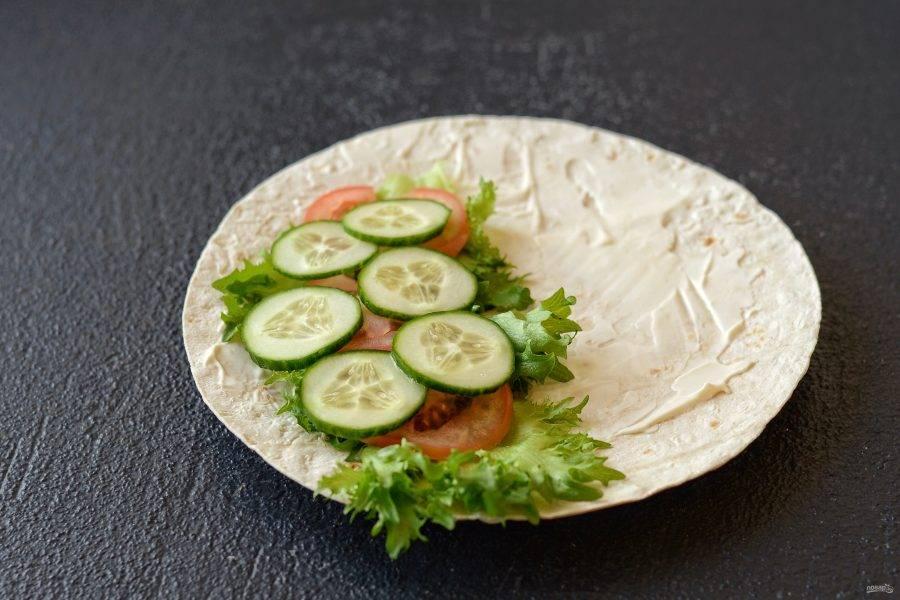 Лаваш смажьте чесночным соусом. На один край выложите листья салата и порезанные на кружочки огурец с помидором.