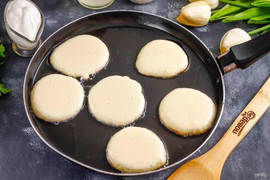 Прогрейте в сковороде растительное масло и убавьте нагрев практически до минимального, так как оладьи будут очень быстро выпекаться. Выложите столовой ложкой части теста в горячее масло.