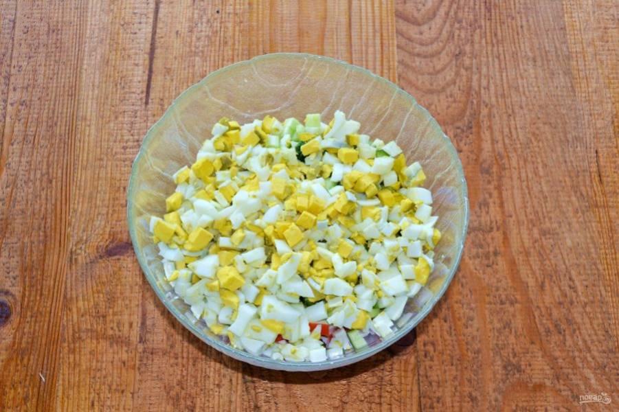 Яйца остудите, очистите и нарежьте кубиками.
