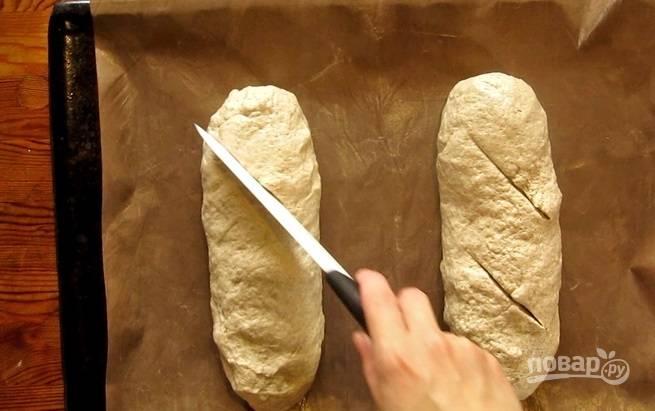 4.Разделите тесто на 2 части и из каждой сформируйте хлеб продолговатой формы, больше напоминающий батон. Сделайте несколько насечек по длине и оставьте хлеб еще на полчаса.