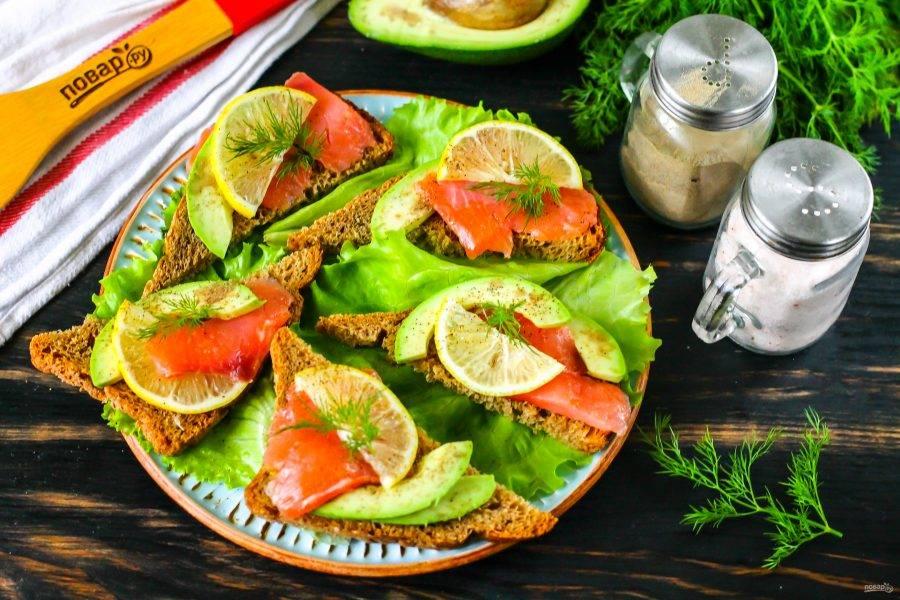 Выложите на тарелку промытые листья салата, а сверху - приготовленные бутерброды и подайте к столу.