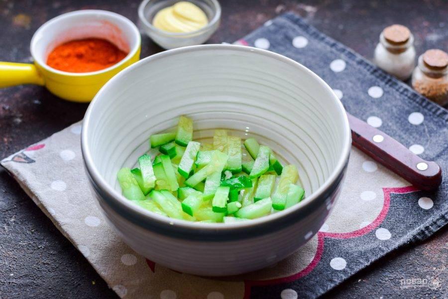 Свежий огурец сполосните и просушите, нарежьте дольками или полосками, переложите в салатник.