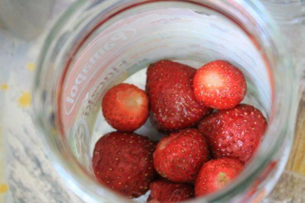 """До верху наполняем стерилизованную банку клубникой. Устанавливаем банку на водяную баню. Банка будет нагреваться, а ягоды оседать вниз. По мере оседания подсыпаем свежие ягоды, пока ягоды """"не усядутся""""."""