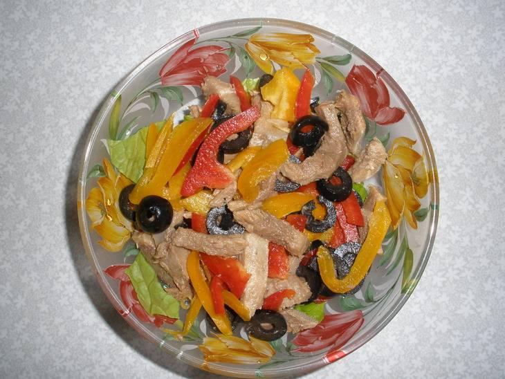 Дожидаемся, пока говяжий язык приготовиться, нарезаем его и кидаем в миску с салатом, перцем и маслинами.