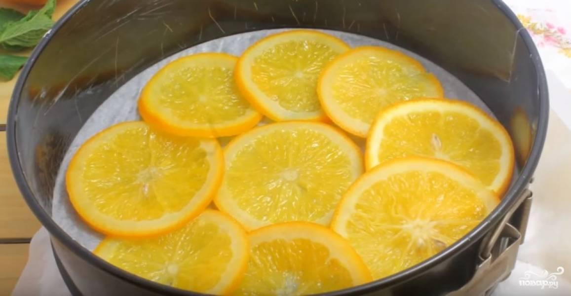 Форму для выпечки застелите пергаментом, на дно выложите проваренные в сиропе апельсиновые кружки. Тут можете поэкспериментировать: от того, как вы выложите апельсины, будет зависеть в итоге внешний вид пирога. Я выкладываю их в виде цветка, это очень просто и в то же время красиво.