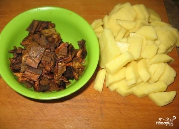 В мясной бульон добавим грибной, доведем до кипения. Грибы порежем на небольшие кусочки, а картофель — небольшими брусочками. Дальше отправляем их в бульон, солим, перчим и варим 10 минут.