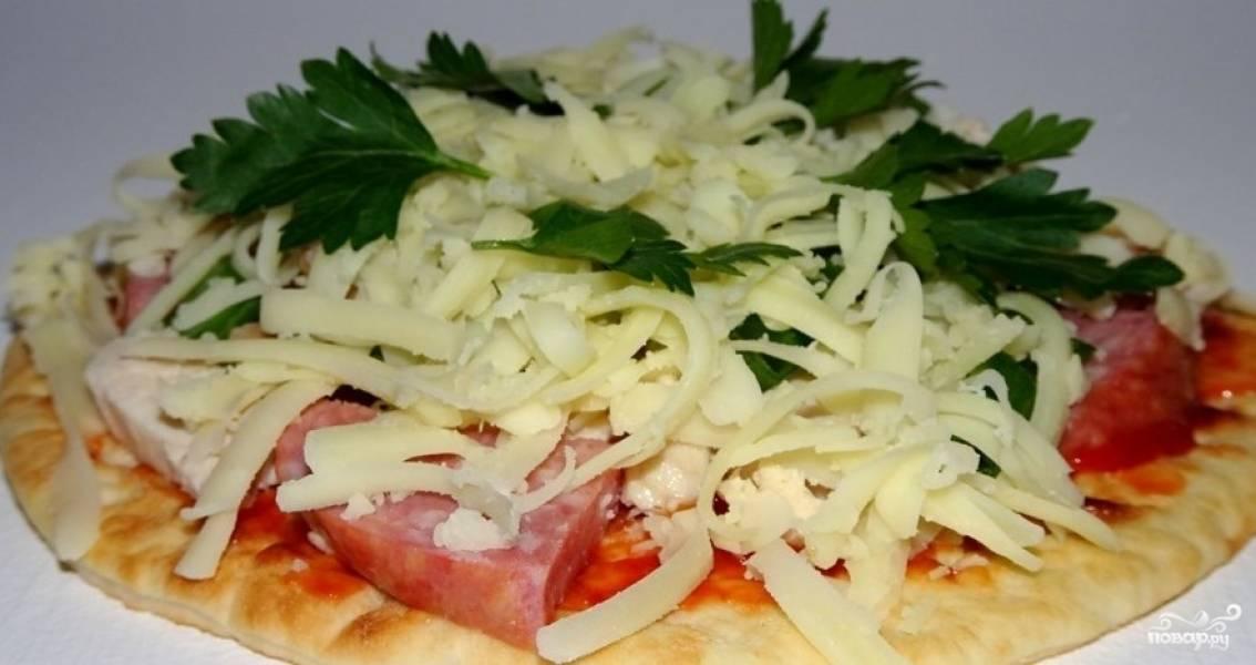 Вместо лаваша или тако также прекрасно подойдут сметанные лепешки. Смажьте их кетчупом, мелко порежьте куриный рулетик и колбасу. Посыпьте ими сверху лепешки, потом натрите сыр поверх и добавьте мелко рубленой зелени по вкусу.