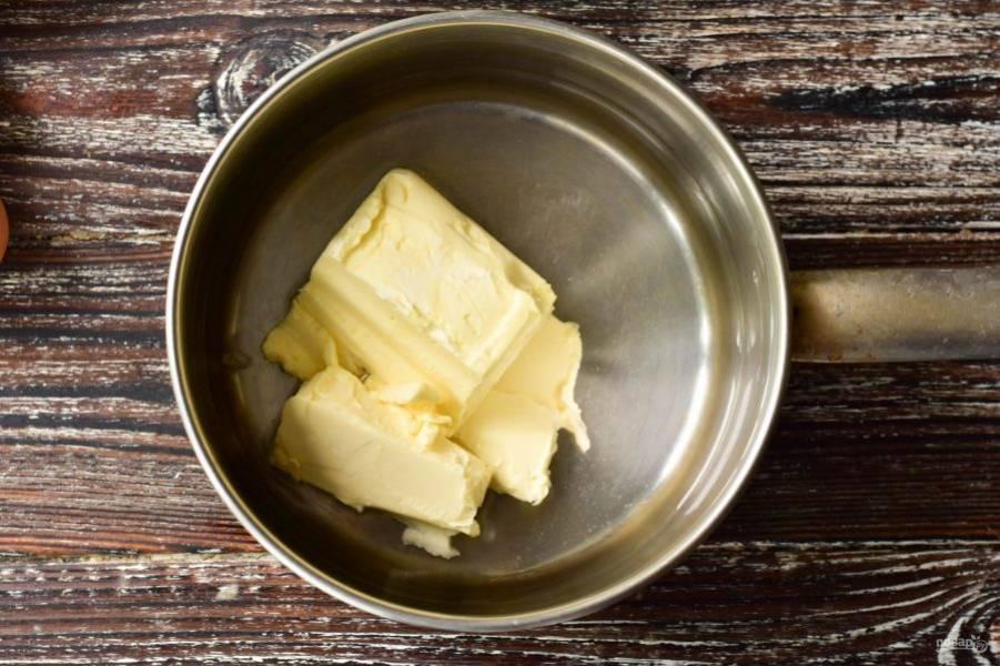 Выложите сливочное масло в ковш, туда же влейте воду и добавьте щепотку соли.