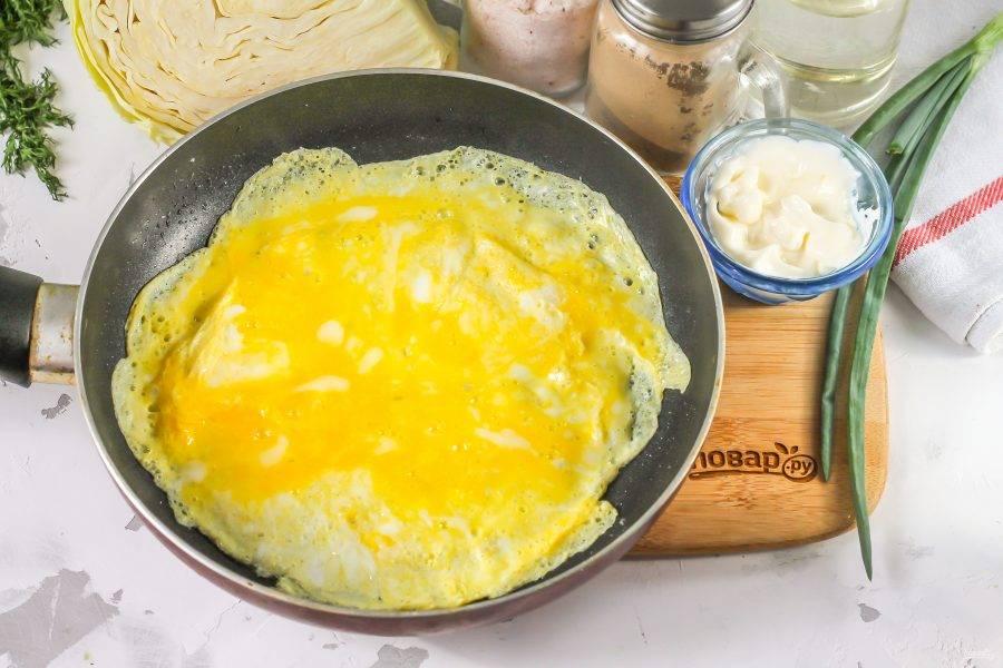 Прогрейте сковороду на плите, влейте растительное масло. Влейте в масло половину взбитой яичной массы и обжарьте блинчик. Точно так же приготовьте второй блин. Остудите их.