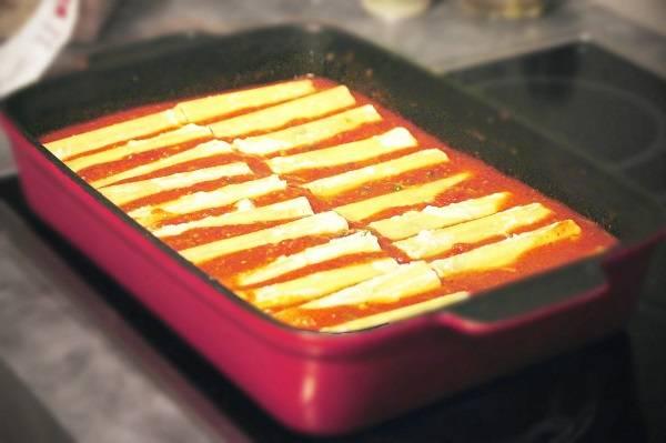 4. Когда все каннеллони уже с начинкой, можно отправить их в форму в подготовленным томатным соусом. Как сделать фаршированные каннеллони, запеченные с сыром, еще интереснее? Можно дополнить блюдо сметанным или сливочным соусом.