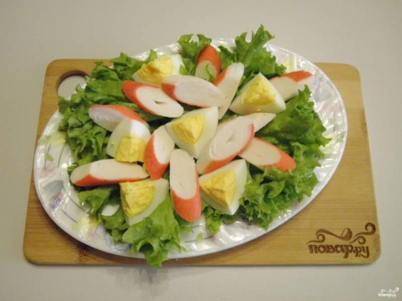 На порционную тарелочку уложите сначала листья салата, а сверху — яйцо и крабовые палочки.
