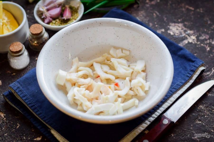 Переложите кальмары в салатник, если кальмары маринованные. Мороженные кальмары предварительно отварите несколько минут, нарежьте.