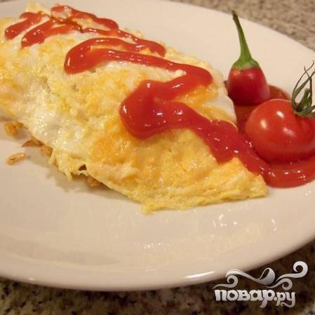 Выложите рис на тарелку и уложите на верх омлет, или заверните рис в омлет. Добавьте пару помидоров черри и подавайте к столу. Приятного аппетита.