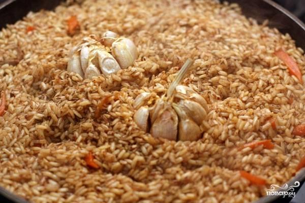 Теперь выкладываем в середину риса головки чеснока и посыпаем его растертой зирой. Накрываем сковородку крышкой и уменьшаем огонь.