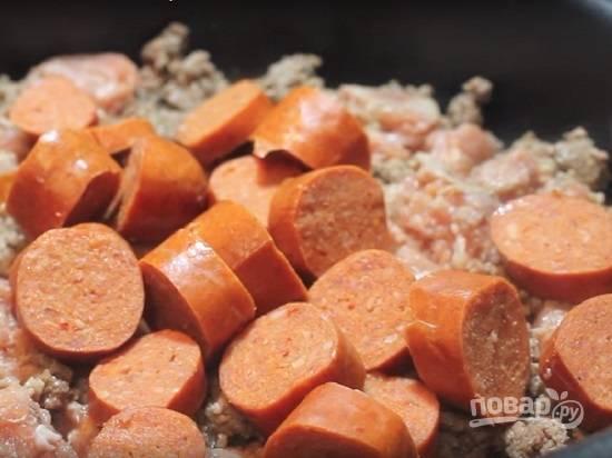 Когда с фарша выпарилась вся жидкость и он начинает подрумяниваться, добавляем к нему колбасу. Жарим минуты 2.