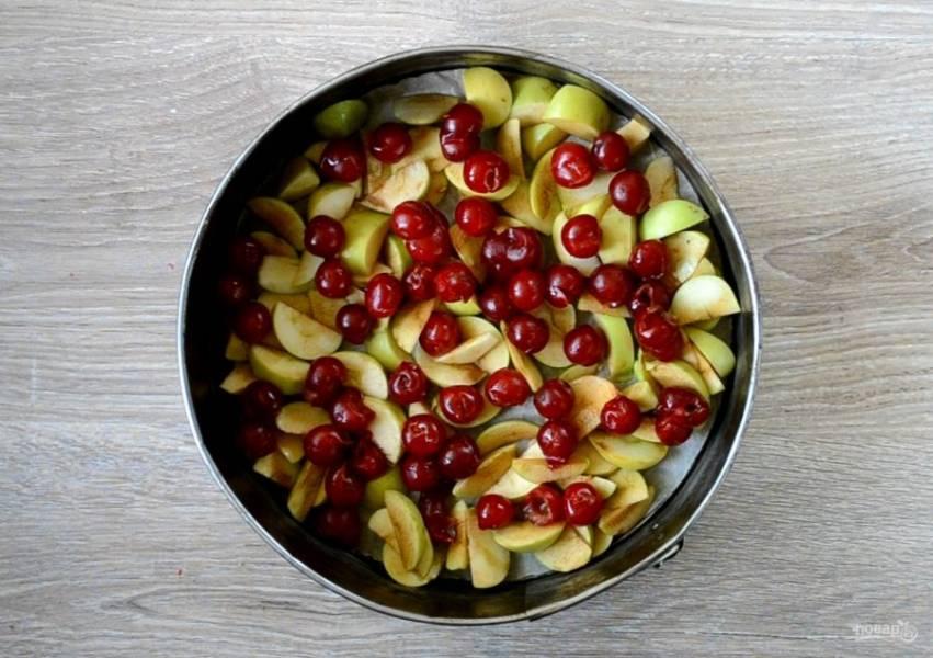 Форму для выпечки (у меня форма диаметром 26 см) застелите пергаментом. На дно ровным слоем выложите дольки яблок и вишню.