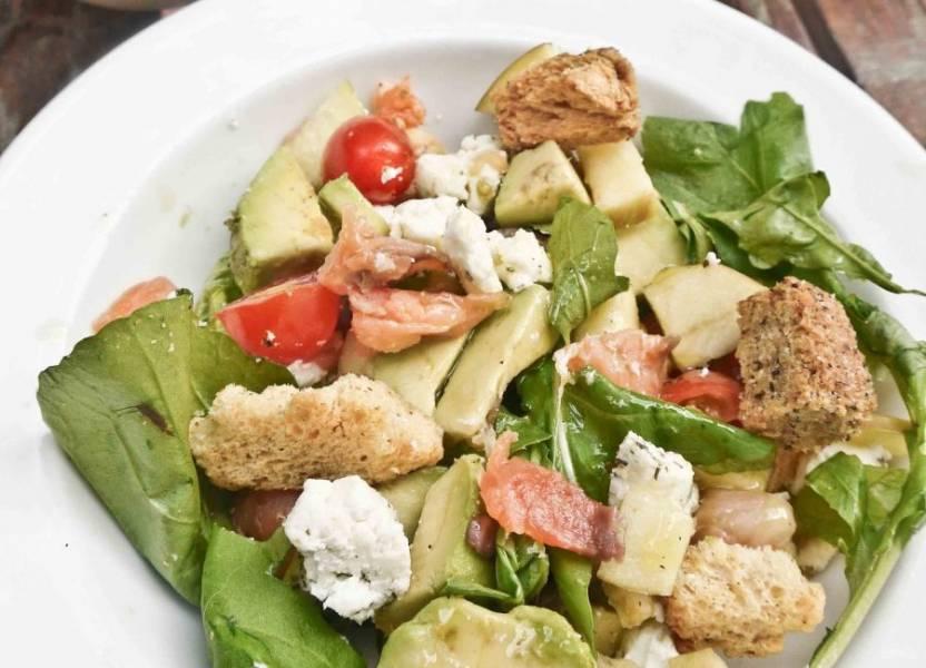 Добавьте в миску с ингредиентами козий сыр, сухарики, авокадо и семгу. Посолите все и заправьте оливковым или любым другим растительным маслом. Перемешайте и подавайте к столу.