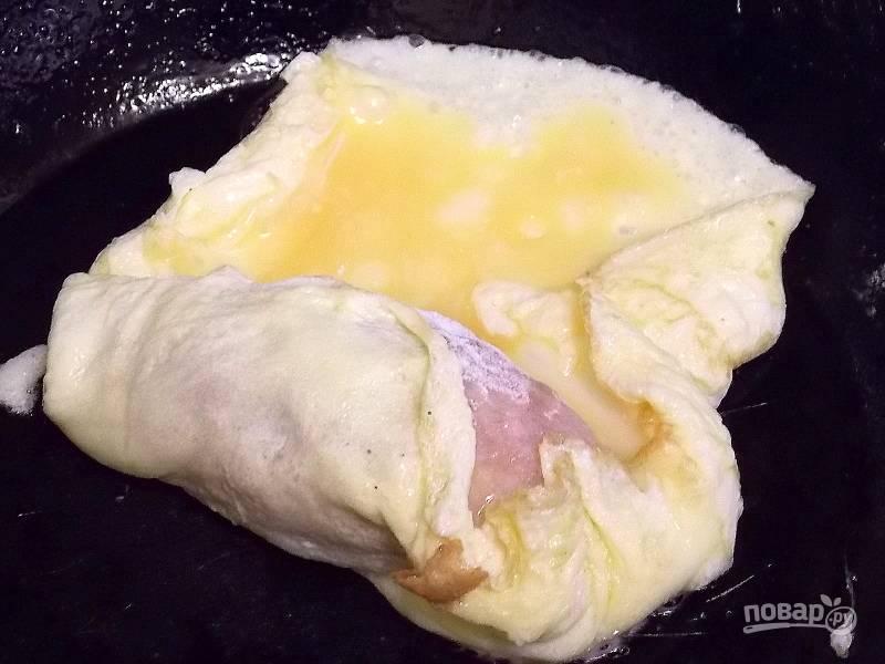 При помощи вилки заверните котлету в яичный блин.