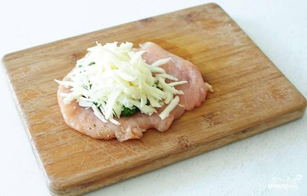 3. Грудку отбейте немного. Выложите ложку соуса, а сверху распределите тертый сыр.