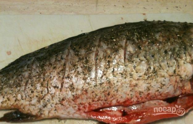 Первым делом подготовьте рыбку. Удалите голову и срежьте плавники. Почистите карпа от шелухи и выпотрошите его. Сделайте поперечные надрезы на тушке с обеих сторон. Натрите рыбу солью и перцем, оставьте мариноваться в холодильнике на несколько часов.