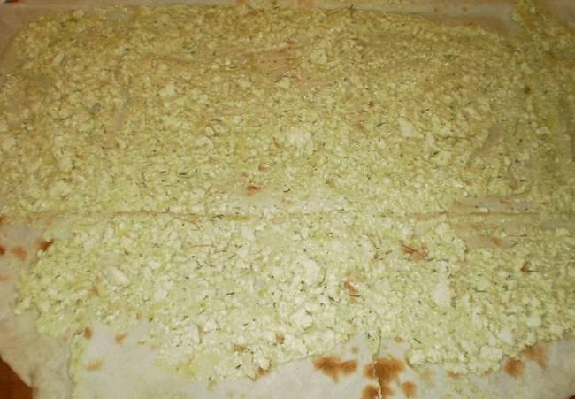 Вилкой разомните авокадо и сыр. Посолите и поперчите. Выложите смесь ровным слоем на лаваш.