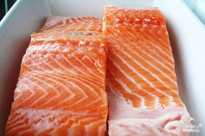 Проверяем рыбу на наличие костей, если таковые нашлись, удаляем их. Нарезаем филе на куски нужной ширины, сбрызгиваем коньяком и укладываем кожей вниз в коробку, в которой и будем солить рыбу. Коньяк придаст рыбке упругость и пикантный вкус.
